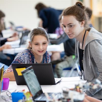 School child working with STFC staff member to code a Lego Mindstorm 'robot'