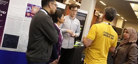Discussion between 5 people at a booth at CIUK conference